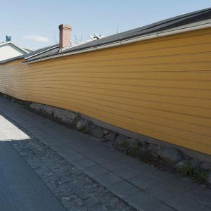 Keltaisen puutalon pitkä lautaseinä Raahessa vanhan kaupungin puutaloalueella