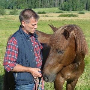 En man och en häst på en äng.