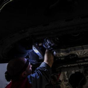 Kuvassa mies työskentelee helsinkiläisellä autohuoltamolla 23. lokakuuta 2020.