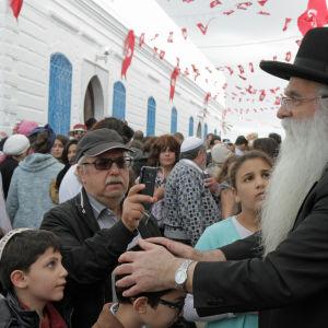 En rabbin på besök från Israel välsignar barn från Djerba.