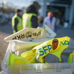 RKP:n vaalitapahtuma. Etualalla RKP:n vaalirekvisiittaa, taustalla kolme ehdokasta epäterävinä.