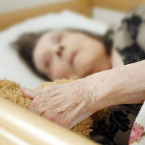 Äldre kvinna ligger i en säng.
