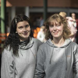 Två flickor ser in i kameran. I bakgrunden syns en skolmatsal.