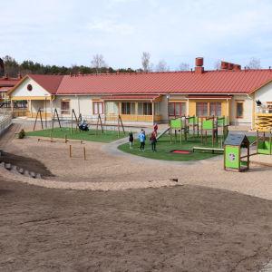 En vit byggnad med rött plåttak. Framför byggnaden finns en lekpark.
