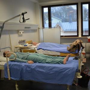 två sjukhussängar med patientdockor