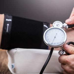 En person mäter blodtrycket.