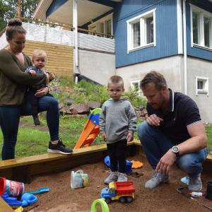 Patrik Grönberg med familj leker i sandlådan.