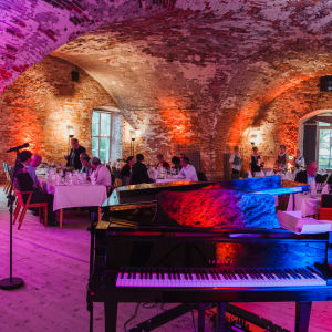 A grand piano in a lit vaulted ceiling restaurant.