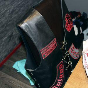 En svart läderväst med texten United brotherhood member i rött.