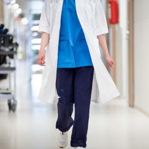 En sjukskötare går i en sjukhuskorridor. Man ser inte huvudet på personen.