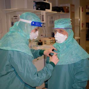 Två sjukskötare i skyddsutrustning.