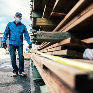 Lasse Lehtinen mittaa ladan pituutta Starkin ulkovarastossa.