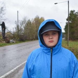 Pojke klädd i blått vid regnig väg