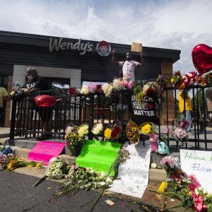 Blommor, hjärtformade ballonger och plakat till minnet av Rayshard Brooks utanför restaurangen Wendy's.