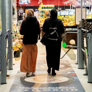Kaksi naista menossa kauppaan.