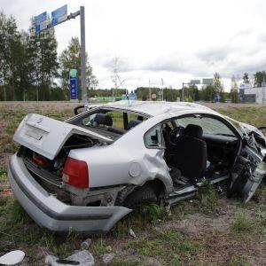Liikenneonnettomuudessa vaurioitunut auto tien sivussa.