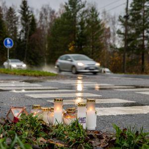 Hautakyntilöitä onnettomuuspaikalla, taustalla suojatie ja kaksi liikkuvaa autoa.