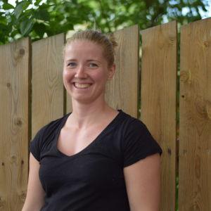 En blond kvinna i svart t-skjorta står vid ett träfärgat staket och ler mot kameran. Sommar.