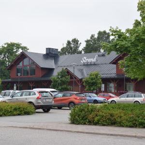 Köpcentret Strand i Ingå. Framför byggnaden står bilar parkerade på en parkering.