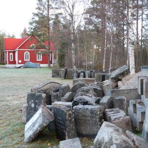 Gravstenar som plockats bort, står i utkanten av Åsändans begravningsplan och det röda kapellet í bakgrunden