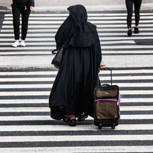 Nainen pukeutuneena burkaan ylittää suojatietä.