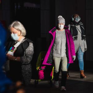 Personer i munskydd i gatubild.