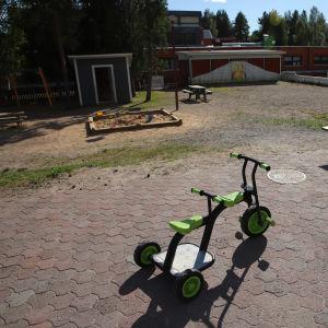 En barntrehjuling står på ett daghems gård.