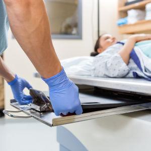Kvinna ligger på sjukhusbrits och ska genomgå röntgenundersökning. I närbild ett par händer med blåa plasthandskar.