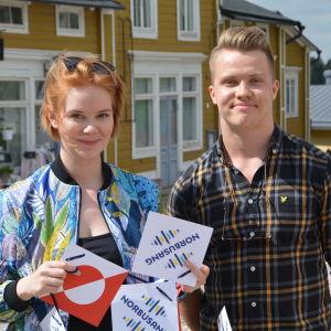 Två personer står i Borgå gamlastad och ler framför trähus.