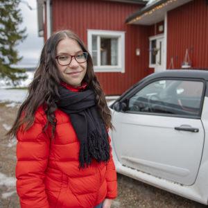 Juulia Ketola mopoautonsa kanssa kotitalon edustalla.