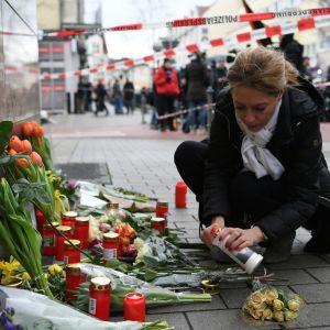 En kvinna lägger ner blommor och tänder ljus vid minnesplatsen i tyska Hanau.