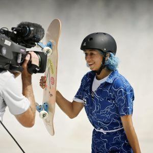 Lizzie Armanto står med sin skateboard framför en kamera.