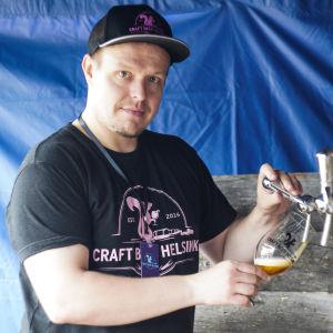 Tero Frosberg häller upp öl från en kran i ett öltält. Han är arrangör för Craft Beer Helsinki.