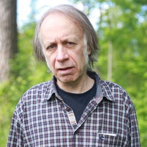 Vanhempi mies katsoo totisena kameraan taustallaan kesäinen metsä.