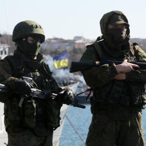 Två maskerade soldater står i en hamn.