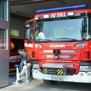 En röd brandbil står vid öppningen till en brandstation.