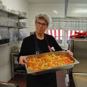 Köksanställd håller i ett tråg med rotfrukter.