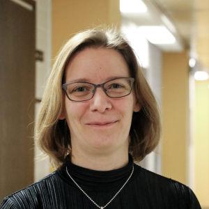 En kvinna med glasögon och axellångt brunt hår står i en korridor.