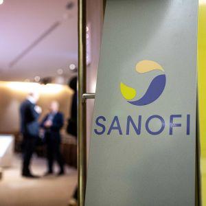 Kuva neuvotteluhuoneen ovelta. Etualalla näkyy Sanofi-lääkeyhtiön logo. Kauempana kaksi tummapukuista miestä keskustelee auditorion etualalla.
