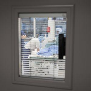 Ikkuna, josta näkyy leikkaussali ja hoitohenkilökuntaa.