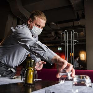 En servitör med munskydd dukar ett bord.