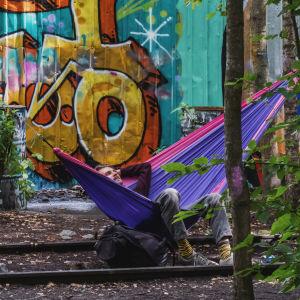 Mies makoilee värikkäässä riippumatossa, joka on kiinnitettynä kahteen junaraiteiden välissä kasvavaan puuhun. Taustalla värikäs graffitimaalaus.
