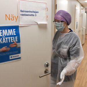 En person med ansiktsskydd, skyddsglasögon, handskar och skyddskläder står vid en dörr.