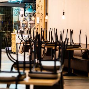Stolar uppochnervända på bord i ett tomt kafé.