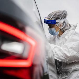 Ett coronatest genomförs vid en drive in-teststation i Helsingfors.