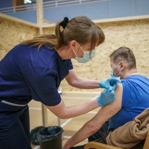 Terveydenhoitaja Johanna Repo antaa koronarokotteen Jyrki Similälle.