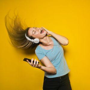 Kvinna med mobiltelefon och hörlurar.