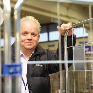 Matkahuollon aluepäällikkö Mika Servanto nojailee pakettirullakkoon