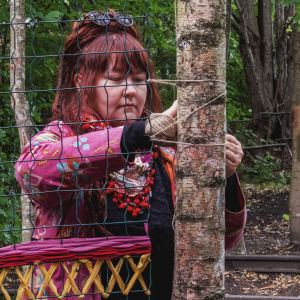 Kvinna i chockrosa och blommig rock och färggrann schal väver ett mönster med färggranna trådar på ett spjälverk som sitter fast mellan två träd.