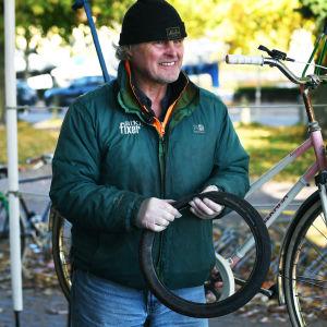 En man håller i ett tomt cykeldäck och tittar förbi kameran. Han står framför en rosa och vit cykel.